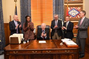 Gov. Hutchinson, center, celebrates after signing the bill.