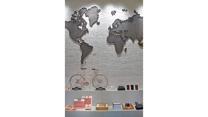 A 1930s world map sculpture hangs over a Shinola city bike
