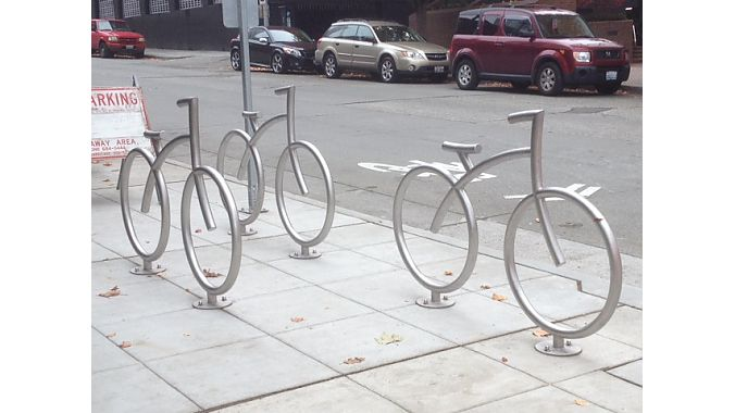 Stylish bike racks outside retailer Velo and apartment high rise Via6