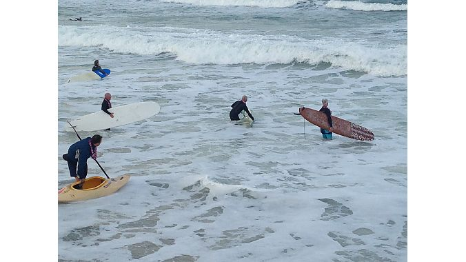 Surfers head out into blustery waters Saturday. Photo: Pat Hus