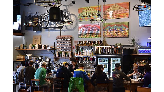 The HandleBar Café and Bike Shop is decorated with bike-themed art, the hand made bar stools and bar top feature bike components, and the bar taps have mountain bike grips for handles. Bikes are displayed throughout the space.