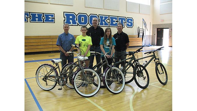 Grand prize bike winners receiving their Raleigh bicycles. From left to right: Scott Cowan (owner of Century Cycles), winner Emma Keane, Chris Speyer (COO of Accell North America), winner Bridget Murphy, and Sean Burkey (Midwest Rep for Raleigh Bicycles).