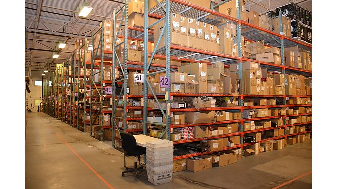 BikeWagon's warehouse is busy and huge. Workers use Raxor scooters to get around sometimes.