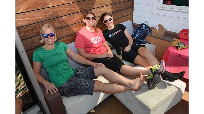 A few of the Ladies of Dealer Tour take advantage of the front patio at Division 1. BRAIN's Val Vanderpool (left) and Megan Tompkins flank Bell Helmets' Kristin Michal.