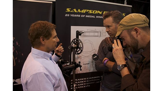 Eric Sampson explains his adjustable pedal to two bike fitters from the Boulder Center for Sports Medicine.