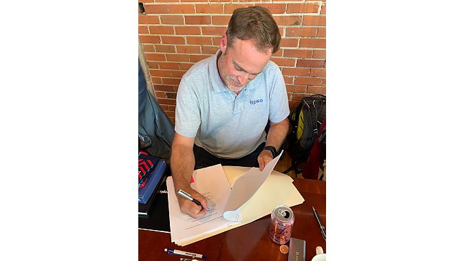 Micklin signs merger papers on Monday. Photo: Ray Keener.
