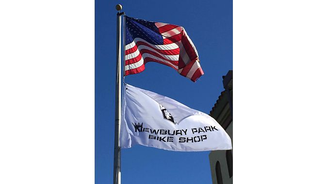 The flagpole from the former post office Newbury Park Bicycle Shop moved into last spring is grandfathered into the building's lease, allowing the shop to fly its banner alongside the Stars and Stripes.