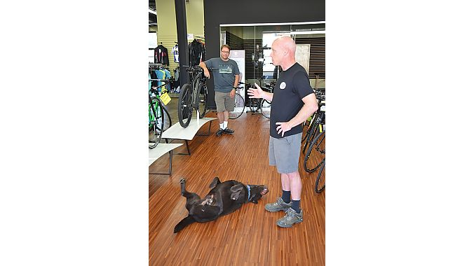 Shop dog Grizzly tried to steal the spotlight as Outspokin' Bicycles' Curran told the BRAIN Dealer Tour crowd about his business.
