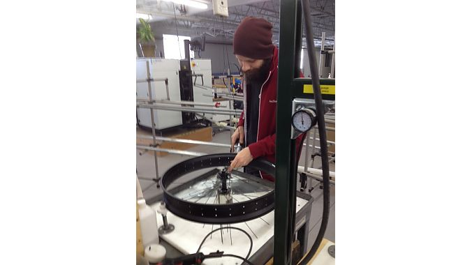 A master wheelbuilder uses a pneumatic tool to place nipples in a fat-bike rim too wide to be accommodated by a Holland wheel-building machine.