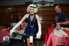 An attendee in her Hollywood glam costume checks out one of the many silent auction items.